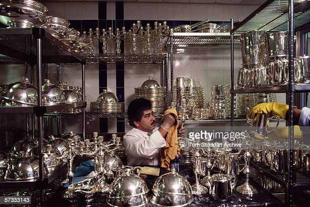 An employee polishing the silver ware. The Dorchester Hotel on London's Park Lane opened its doors on April 18th 1931. Since then the name has become...