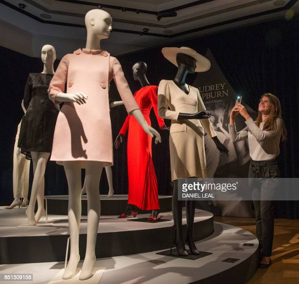 An employee poses alongside a display of outfits during a preview of Audrey Hepburn's personal collection at Christie's auction house in central...