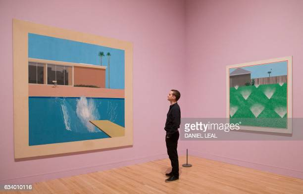 An employee poses alongside artworks entitled 'A Bigger Splash 1967' and 'A Lawn Being Sprinkled 1967' by British artist David Hockney during a...