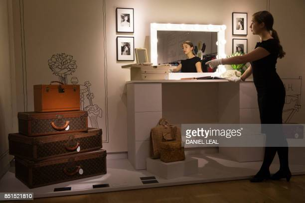 An employee poses at a dressing table displaying a Jewellery Box circa 1970 with a reserve price of £1000 £1500 and a Swiss whiteplastic rotary dial...