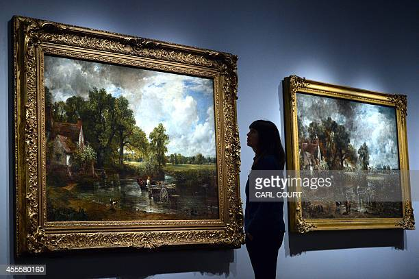"""An employee poses between paintings by British artist John Constable entitled """"The Hay Wain"""" and """"The Hay Wain """" during a photocall at the Victoria..."""