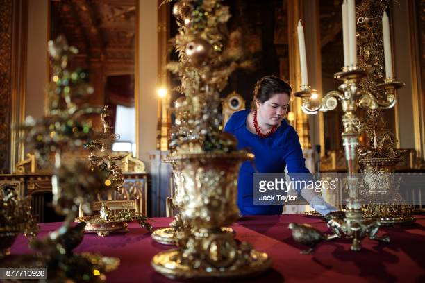 An employee poses by the table in the State Dining Room which has been decorated for the Christmas period with silvergilt pieces from the Grand...