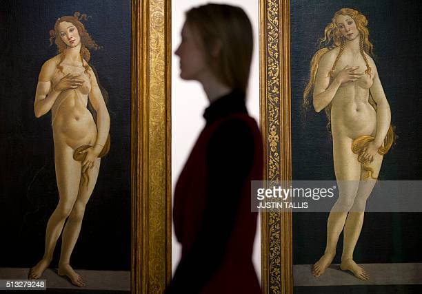 An employee poses for a photograph between 'Venus 1490' and 'Venus 1490' both by Italian painter Sandro Botticelli during a photocall at the Victoria...