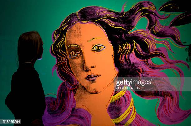 An employee poses for a photograph next to 'Sandro Botticelli Birth of Venus 1484' by US artist Andy Warhol during a photocall at the Victoria and...