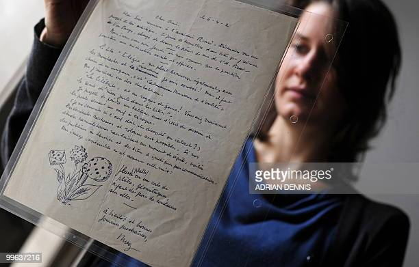 An employee poses for photographers with a letter by surrealist artist Rene Magritte during a photocall at Sotheby's in London on May 17 2010...