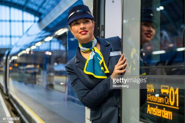 An employee poses for photographs in the doorway of a Eurostar International Ltd passenger train during the inauguration of the London to Amsterdam...