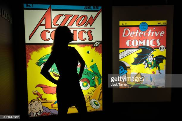 An employee poses in front illuminated displays of the first comics to feature Superman and Batman at the DC Comics Exhibition Dawn Of Super Heroes...