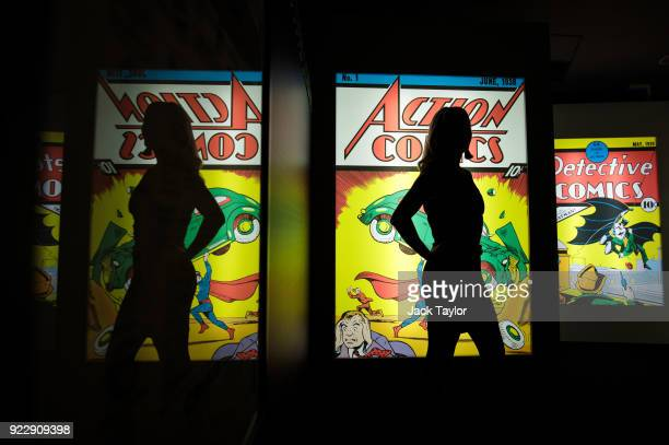 An employee poses in front illuminated displays of the first comics to feature Superman and Batman at the DC Comics Exhibition: Dawn Of Super Heroes...