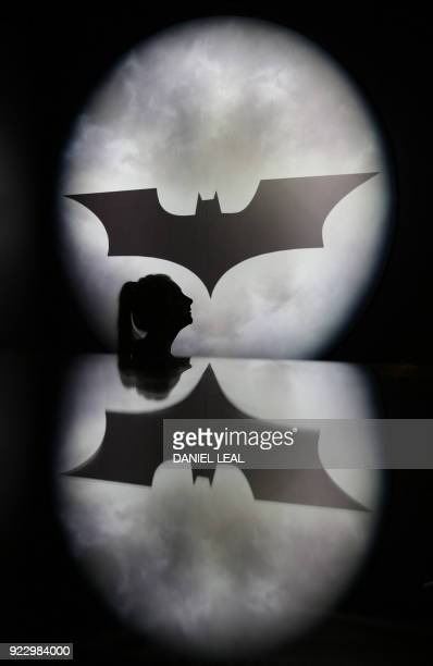 An employee poses in front of a Batman logo during a press preview of 'DC Comics Exhibition: Dawn of Super Heroes' at the O2 Arena in Greenwich, east...