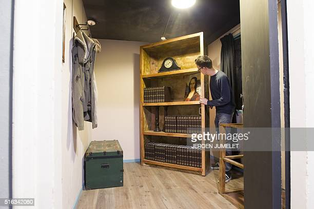 An employee poses in Valkenswaard on March 18 2016 at the Escape Bunker replica of the place where Anne Frank and her family went into hiding in...