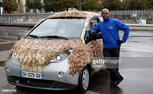 An employee poses next a car named Cavalcade one of the nine new customized Autolib cars on October 8 2014 in Paris France on October 8 2014 in Paris...