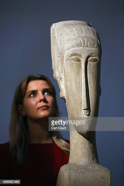 An employee poses next to a sculpture by Amedeo Modigliani entitled 'Tete' during a press preview at Sotheby's on October 10, 2014 in London,...
