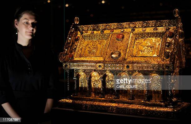 An employee poses next to an early 1100's Flemish reliquary of 'The shrine of St Amandus' at the British Museum in central London on June 21 2011...