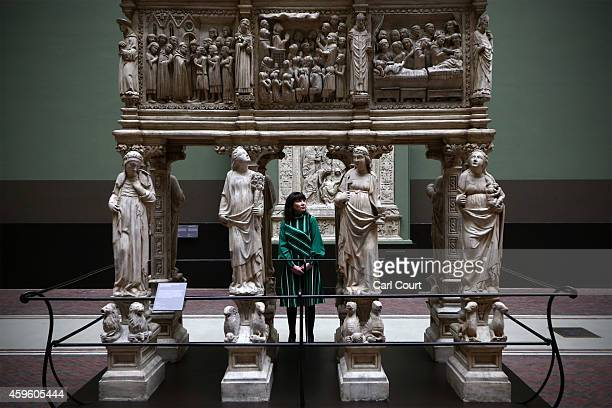 An employee poses next to an exhibit entitled 'Tomb of St Peter Martyr' by Giovanni di Balduccio and dated 1338 during a press preview for the newly...