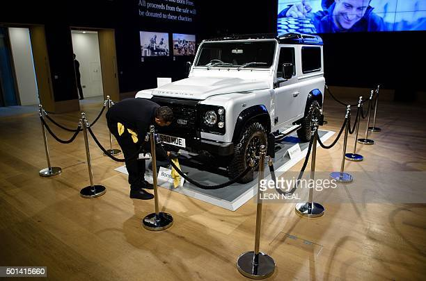 An employee poses next to the twomillionth Land Rover Defender offroad vehicles during a photocall promote the forthcoming charity auction of it at...