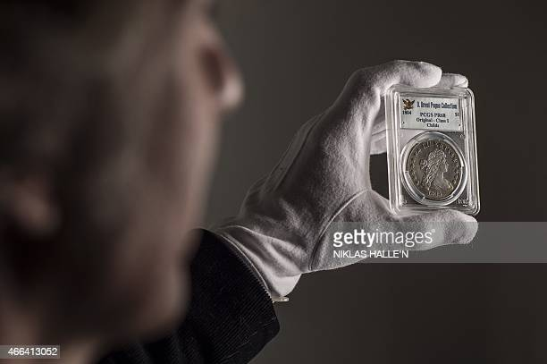 An employee poses with a 1804 Silver Dollar coin during a photo call at Sotheby's auction house in central London on March 13 2015 The coin is part...