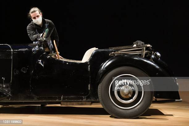 An employee poses with a 1937 Bugatti Type 57S, nicknamed 'Dulcie' due to its registration number 'DUL 351' at Bonhams in central London on February...