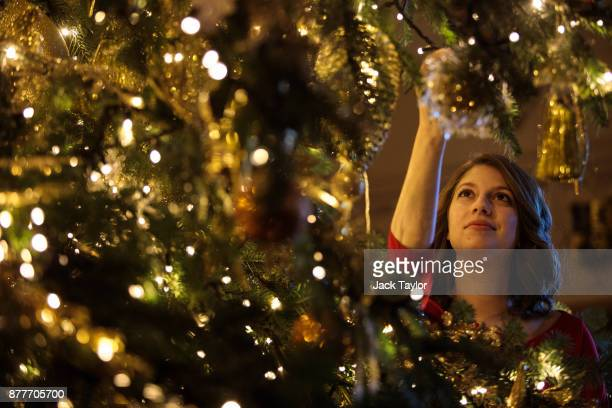 An employee poses with a 20ft Nordmann Fir tree from Windsor Great Park in St George's Hall which has been decorated for the Christmas period on...