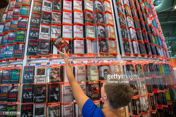 An employee poses with a book as she prepares the stand of Droemer at the Frankfurt Book Fair on October 15, 2019 in Frankfurt am Main, Germany. The...