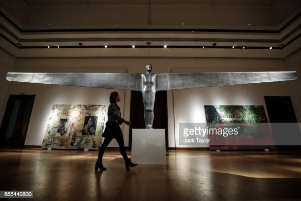 An employee poses with 'A Case for an Angel I' 1989 by Antony Gormley at Christie's London on September 29 2017 in London England Christie's Auction...