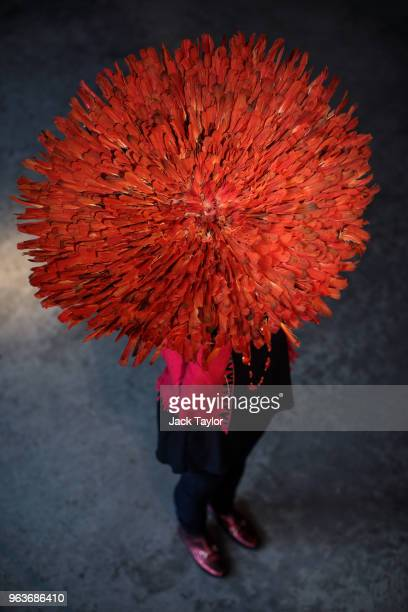 An employee poses with a ceremonial feather hat 'JuJu or Tyn' from the Bamileke people Grasslands Cameroon 1970s during a press preview at Summers...