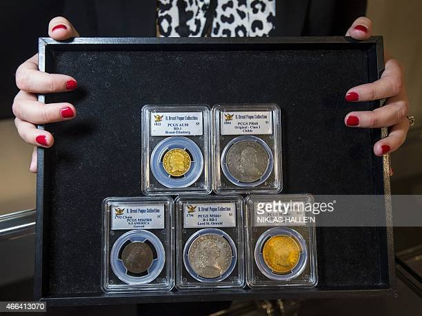 An employee poses with a collection of coins during a photo call at Sotheby's auction house in central London on March 13 2015 The coins are part of...