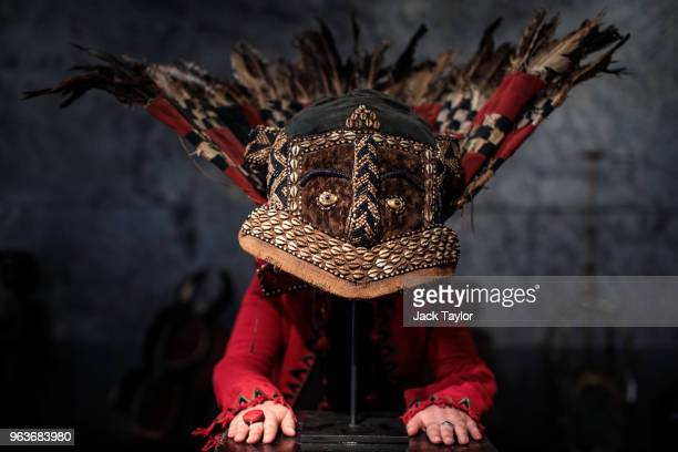 An employee poses with a feathered helmet mask 'Mwaash aMbooy mu shall' from the Kuba people DRC 19th century during a press preview at Summers Place...