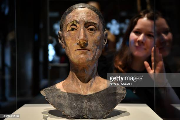 An employee poses with a funeral effigy head of King Henry VII 1509 during the press launch of the The Queen's Diamond Jubilee Galleries in...