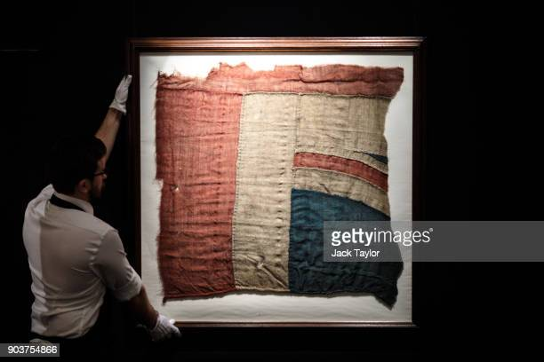 An employee poses with a large fragment of the Union Jack flag believed to have flown from Lord Horatio Nelson's ship the HMS Victory at the battle...