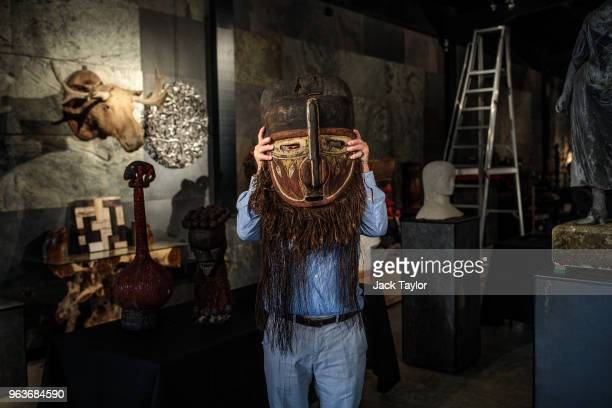 An employee poses with a large painted wood ceremonial mask during a press preview at Summers Place Auctions on May 30 2018 in Billingshurst England...