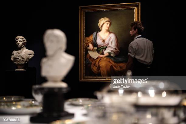 An employee poses with a portrait of Emma Hamilton as Sibyl by Gavin Hamilton beside a marble bust of Lord Horatio Nelson circa 1800 during a photo...