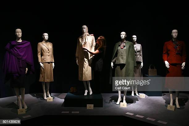 An employee poses with an Aquascutum Fawn Gaberdine Raincoat and scarf during a press preview at Christies auction house on December 15 2015 in...