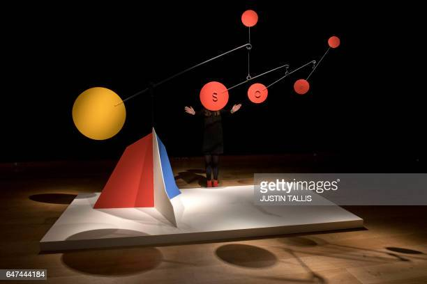 An employee poses with an artwork by American sculptor Alexander Calder entitled Untitled with an estimated price of 3555 million GBP during a...
