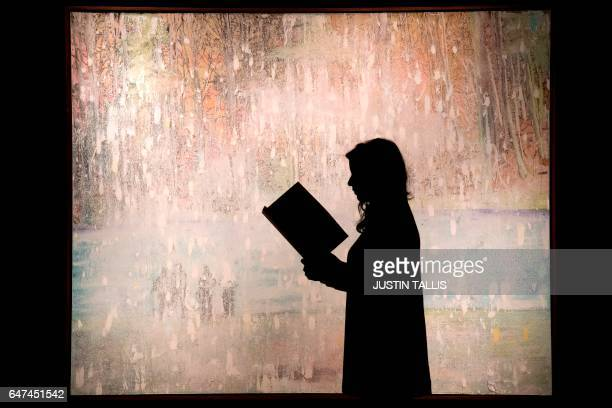 An employee poses with an artwork by British artist Peter Doig entitled 'Cobourg 3 1 More' with an estimated price of 812 million GBP during a...