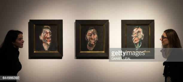 An employee poses with an artwork by Irishborn British artist Francis Bacon entitled Three Studies for a Portrait of George Dyer with an estimated...