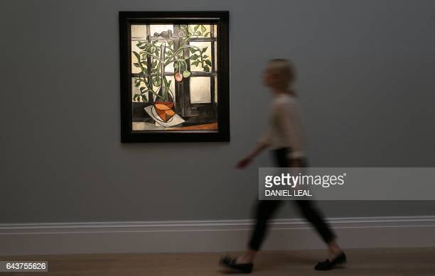 An employee poses with an artwork by Spanish artist Pablo Picasso entitled 'Tomato Plant 1944' with an estimated price of 1015 million GBP during a...