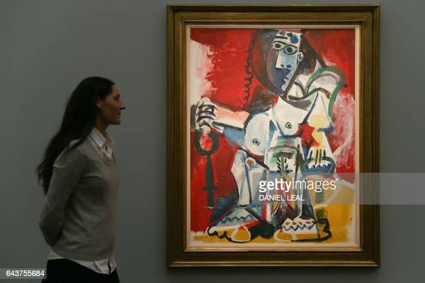 An employee poses with an artwork by Spanish artist Pablo Picasso entitled 'Femme new assise 1965' with an estimated price of 95125 million GBP...