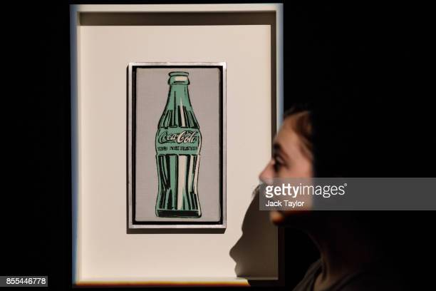 An employee poses with 'Coke Bottle' 1962 by Andy Warhol at Christie's London on September 29 2017 in London England Christie's Auction House is to...