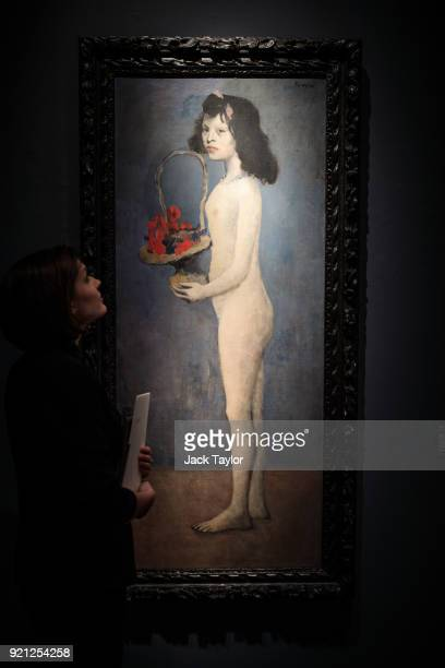 An employee poses with 'Fillette a la corbeille fleurie' 1905 by Pablo Picasso during a photocall for the Peggy and David Rockefeller art collection...