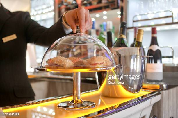 An employee positions a cloche over sandwiches in the lounge bar on board an Airbus SE A380800 passenger aircraft operated by Emirates Airlines...