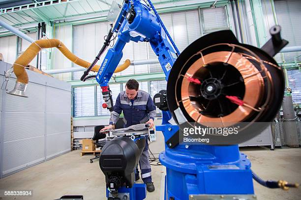 An employee positions an automotive part as a Yaskawa Electric Corp robotic arm operates inside the research and development department at...