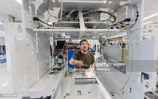 An employee positions the head module unit automated teller machine on the production line at Wincor Nixdorf AG in Paderborn Germany on Thursday July...