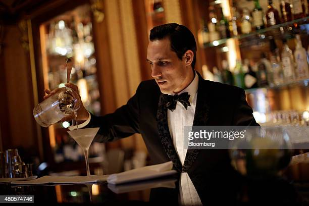 An employee pours a cocktail in the Library Bar inside the Lanesborough luxury 5star hotel operated by the Oetker Group following renovation and...