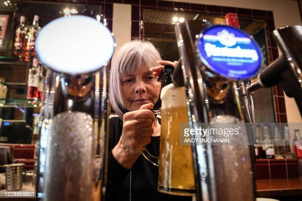 An employee pours a draught beer in Jackson's Bar in the city centre of Glasgow on October 8 on the eve of a two-week closure of pubs due to an...
