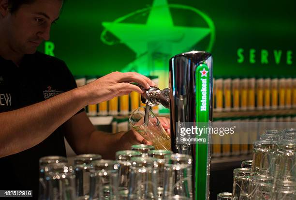 An employee pours a glass of draught Heineken lager beer for a customer in the Heineken NV Experience bar in Amsterdam Netherlands on Friday July 31...