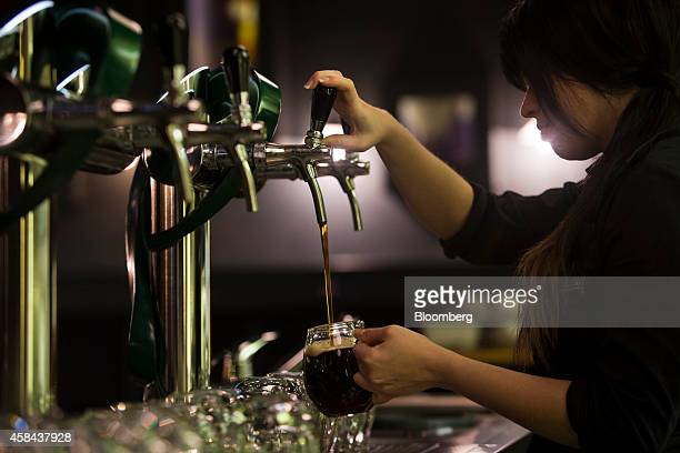 An employee pours a glass of Staropramen beer from a tap dispenser in the visitor's center bar at the Pivovary Staropramen AS brewing company...