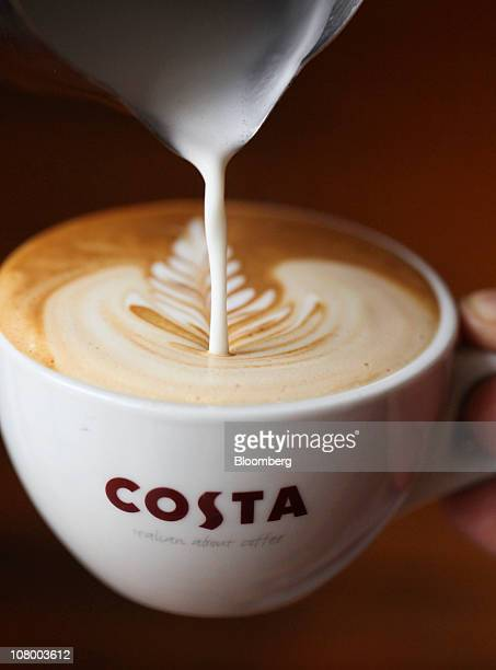 An employee pours a 'rosetta' pattern in to a cup of coffee at the Costa Coffee central storage facility in London UK on Wednesday Jan 12 2011...