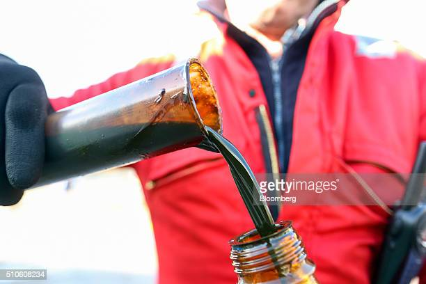 An employee pours a sample of oil from a bottle into a measuring vessel at UK Oil and Gas Investments Plc's drilling site in Horley UK on Tuesday Feb...