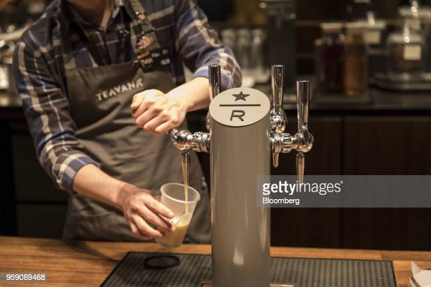 An employee pours a Teavana tea beverage from a tap inside the Starbucks Corp Reserve Roastery store in Shanghai China on Friday May 11 2018...