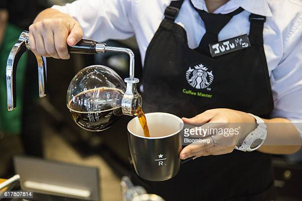 An employee pours coffee from a round glass jug into a mug at a Starbucks Corp coffee shop in Phnom Penh Cambodia on Monday Oct 24 2016 The...